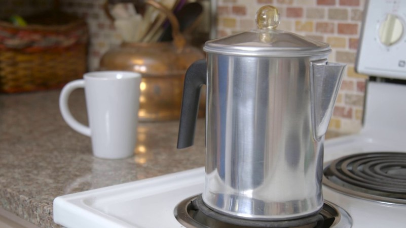Metal percolator on stove top in front of white mug.