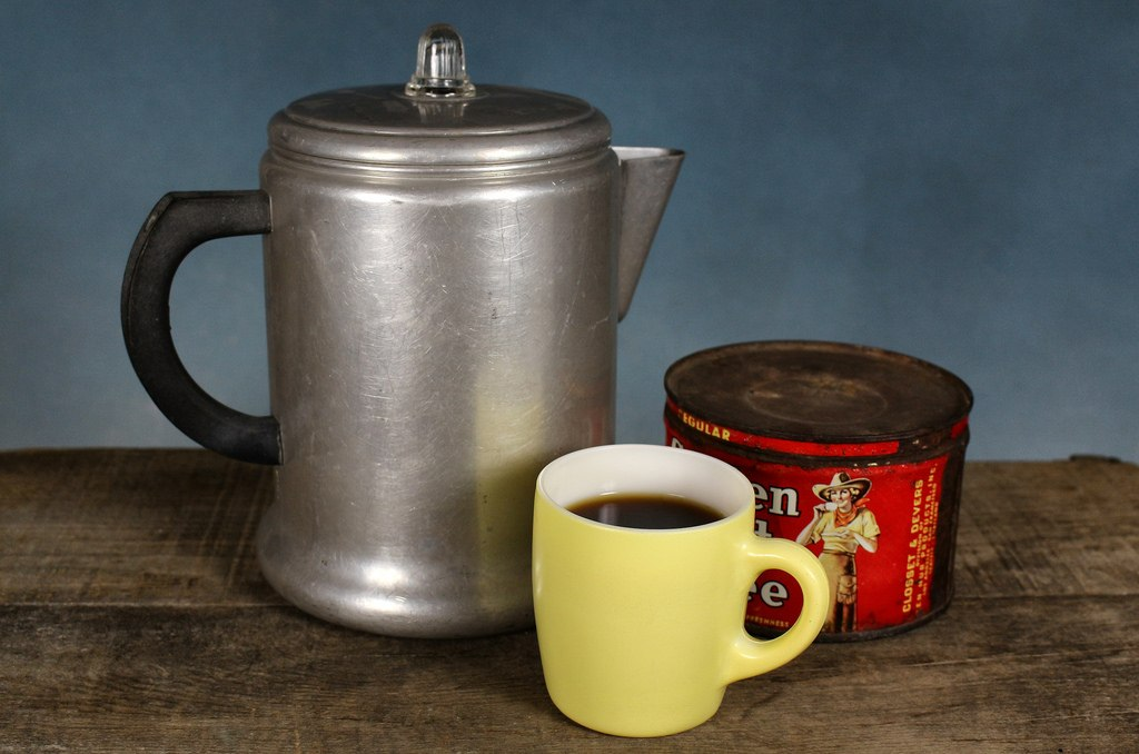 Old percolator with ground coffee and mug