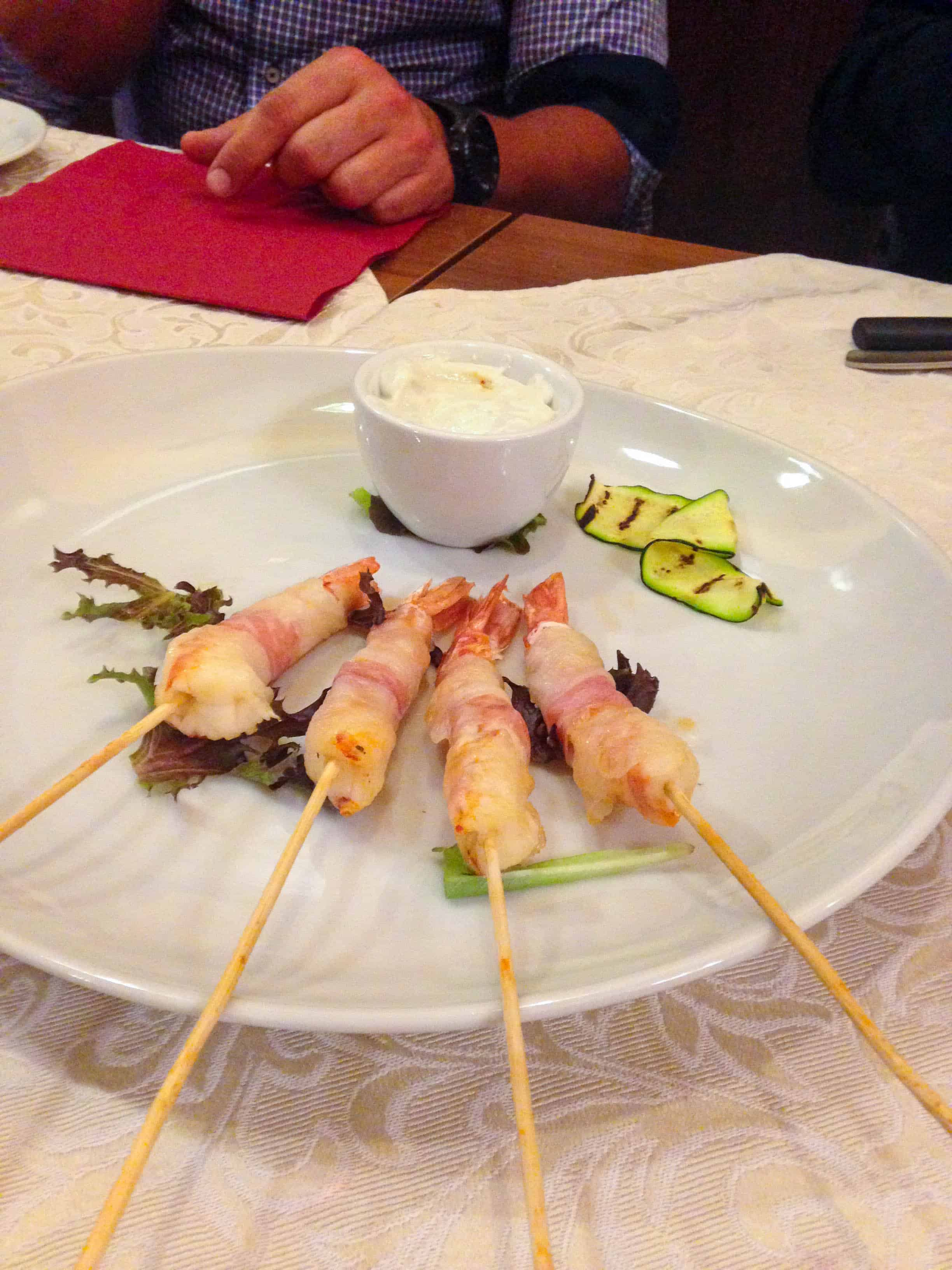 shrimp wrapped in lardo with gorgonzola sauce in Torino, Italy
