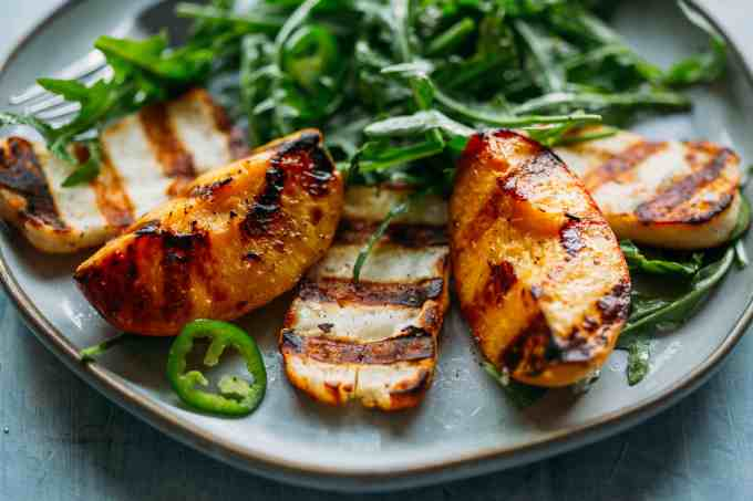 close up of grilled halloumi and peaches with arugula, jalapeños and honey lemon vinaigrette