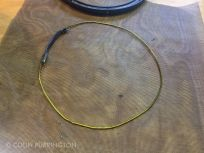 Bend coat hanger into diameter equal to inside diameter of pail.