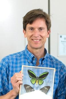 Photograph of Colin Purrington. Holding a framed Ornithoptera priamus.