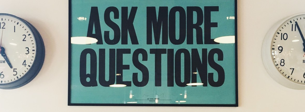 "sign on a wall that says ""Ask More Questions"""