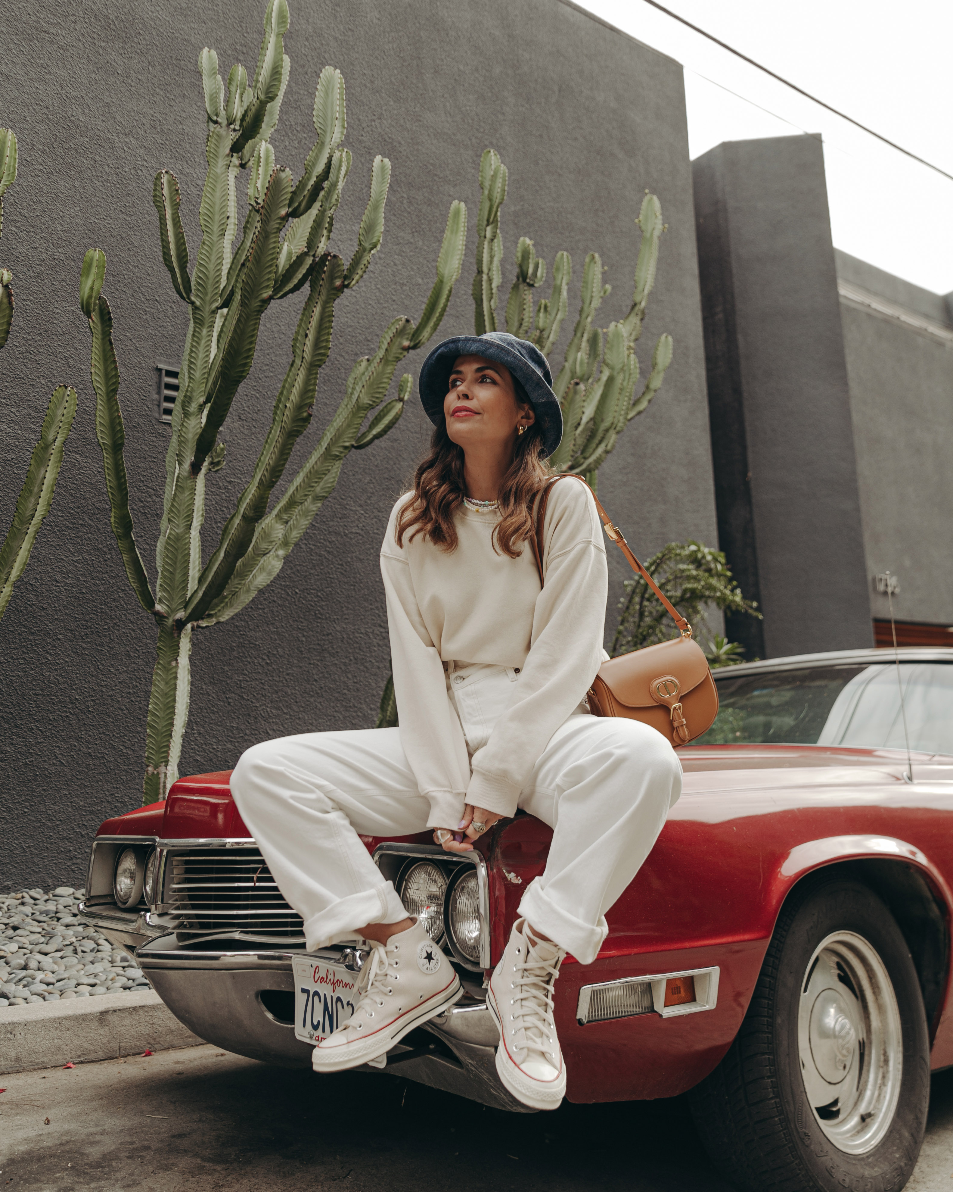 Sara from Collage Vintage wearing Agolde white jeans, Dior denim bucket hat and Converse All-Star