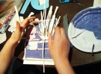 Daniela peinando los flecos hechos con trozos de páginas
