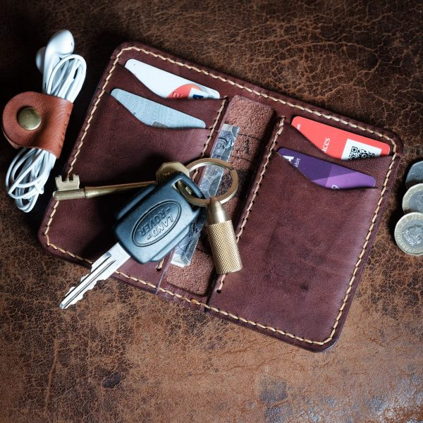 Flatlay of Whinlatter hand made leather wallet with coins and keys and other EDC items