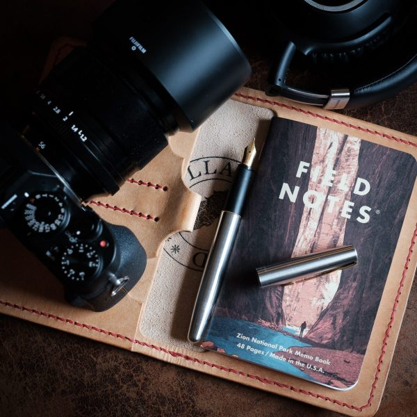 Special Edition National Parks Field Notes and Passport Cover in Badalassi Carlo Bone Natural Pueblo Leather, with fountain pen and red saddle stitching.