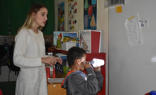 Alexis Shelly watches as a student projects his constellation onto a classroom wall.
