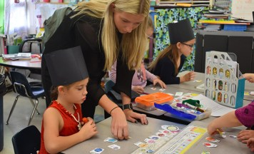Elizabeth Pardon helps a student sort her planets before gluing them to her solar system hat.