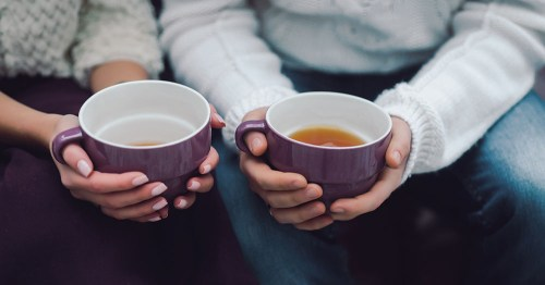 Two people holding cups of tea