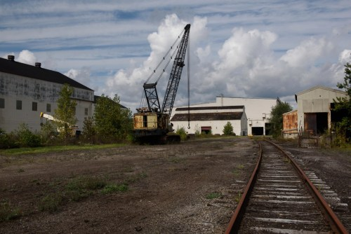 Rusty remains and railroad tracks sit quiet at the Casey Industrial Park