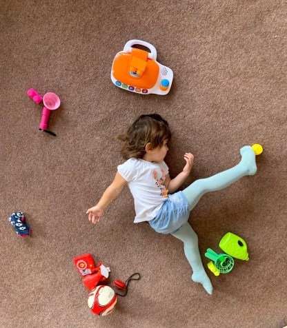 Pre-schooler stretching towards colourful props