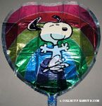Snoopy dancing in front of rainbow heart-shaped Clear Mylar Balloon