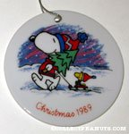 Snoopy holding tree and Woodstock on sled Ceramic Ornament