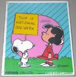 Snoopy holding sign with Lucy 'This is national dog week' Puzzle