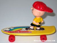 Charlie Brown standing on yellow skateboard