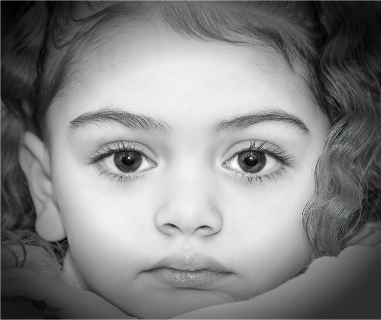 Full face of little girl with large eyes staring straight at you
