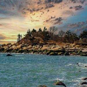 Beautiful sunset at the rugged shoreline of Hammonasset Beach in the winter