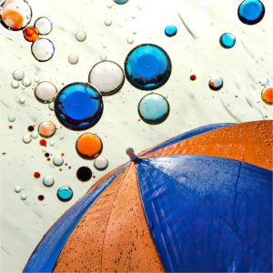 Colored water drops floating down to orange and blue umbrella