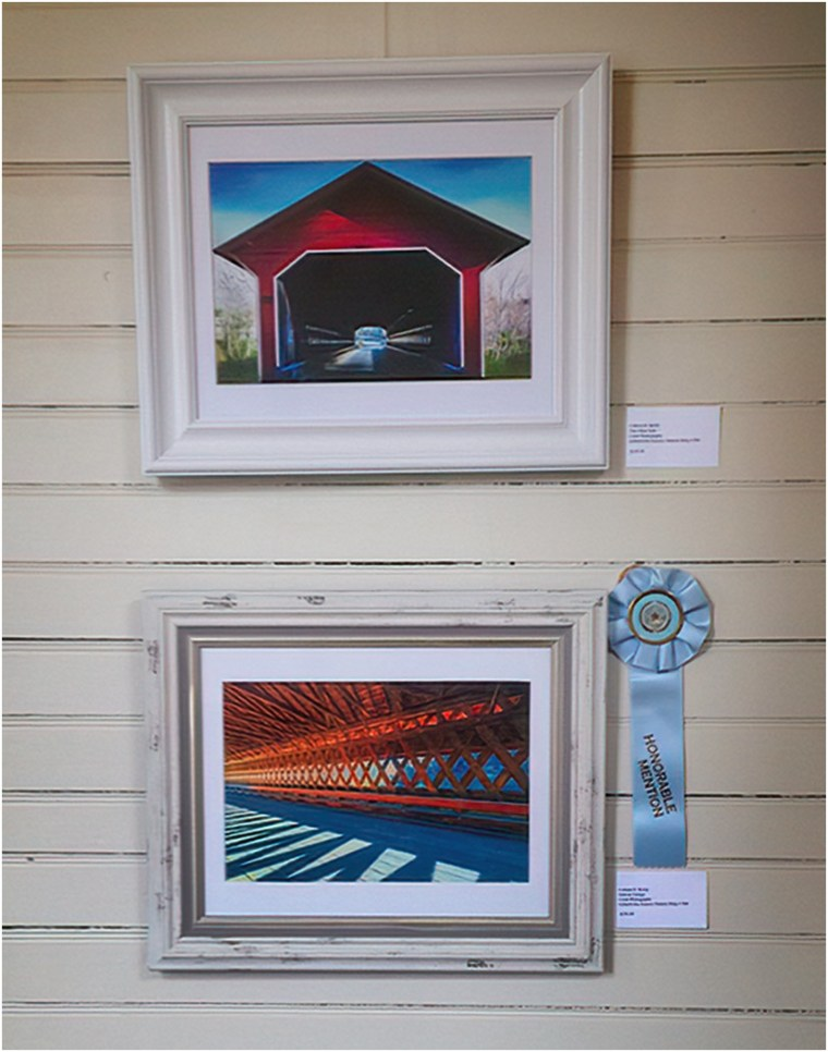 "Two framed submissions on wall for photo exhibit, ""New Views of Gilbertville"""