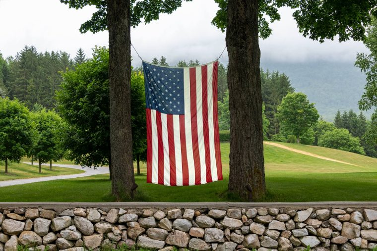 Large American flag waving between 2 trees in Vermont during summer