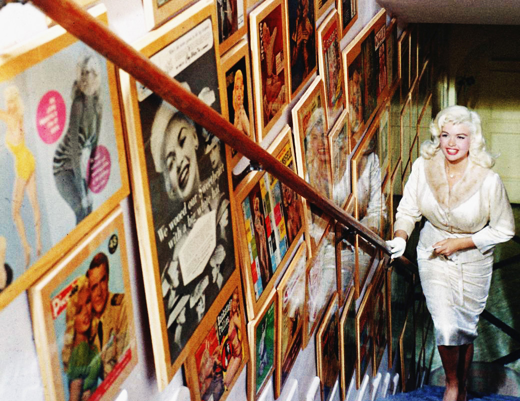 Jayne Mansfield's Pink Palace | Jayne walks up the stairs of her home, decorated with framed magazine covers.