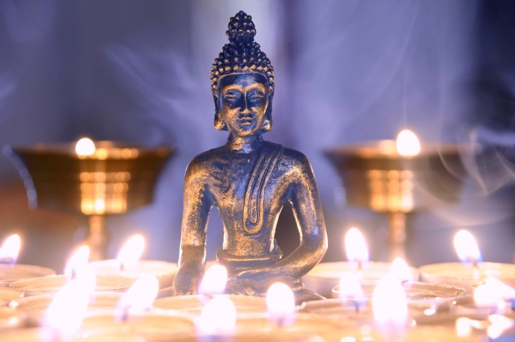 Buddah statue surrounded by lit candles
