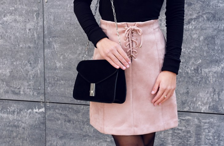 Woman wearing pink suede lace up mini skirt black bag and black long sleeve top