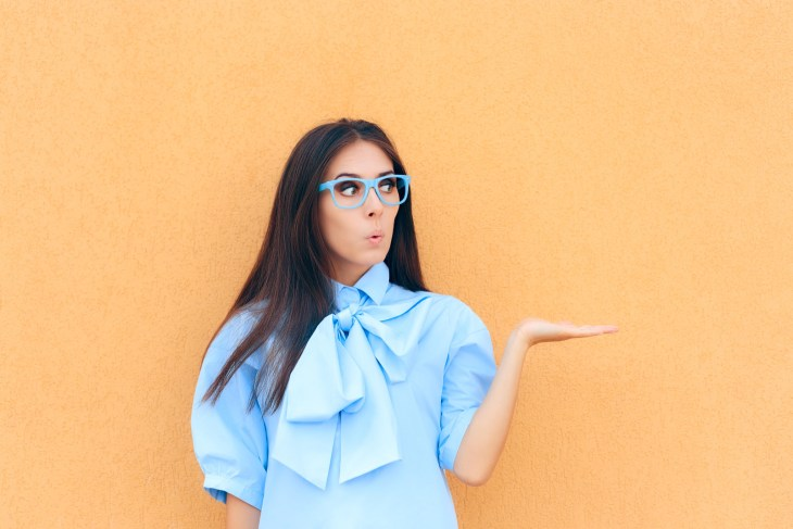 Women in a blue shirt and glasses standing in front of yellow wall