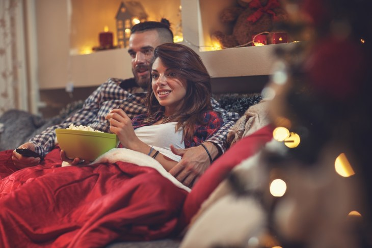 Couple watching movies on the couch under a blanket