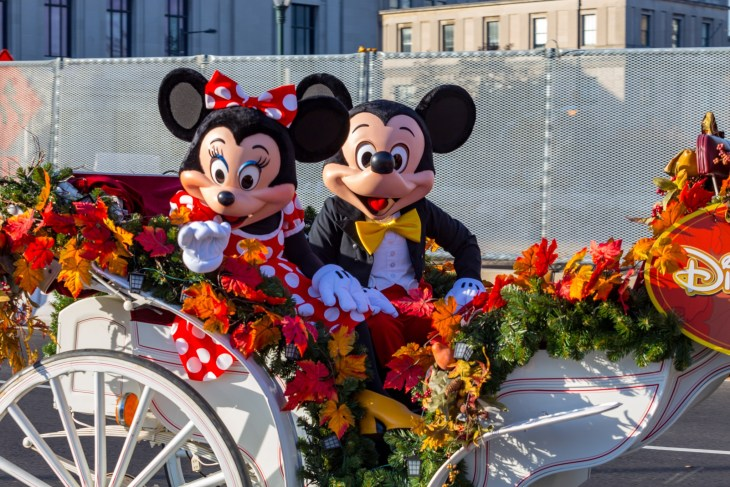Mickey and Minnie Mouse on carriage with flowers around them