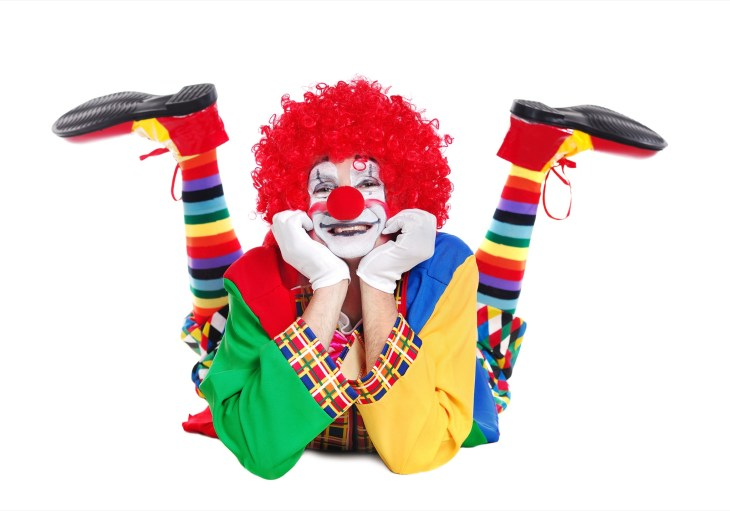 Happy clown laying on the floor with legs up and a white background