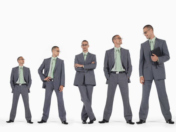 Row of business men in ascending order of height against white background