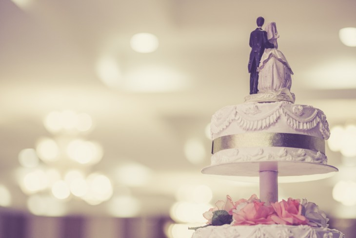 A woman and man figurine on top of a wedding cake