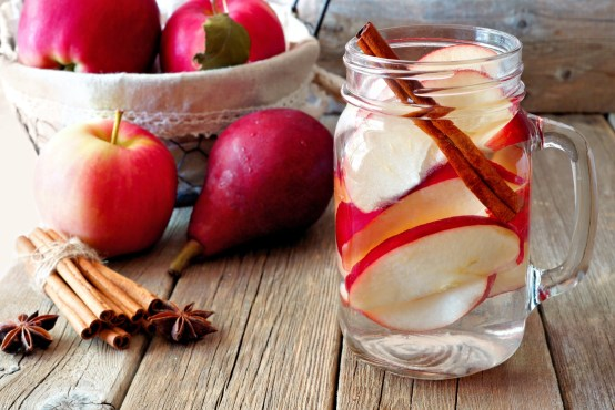 Glass of water with slices of apple and cinnamon sticks on wooden table