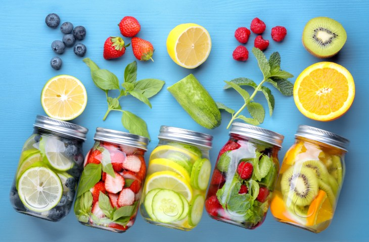 Mason jars filled with infused water with different fruits and herbs on blue background