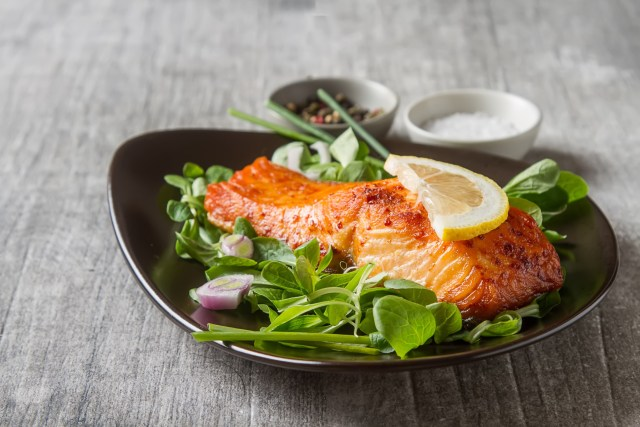 A plate of salmon, topped with lemon and greens