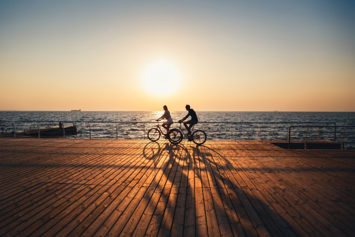 Two people cycling by the beach