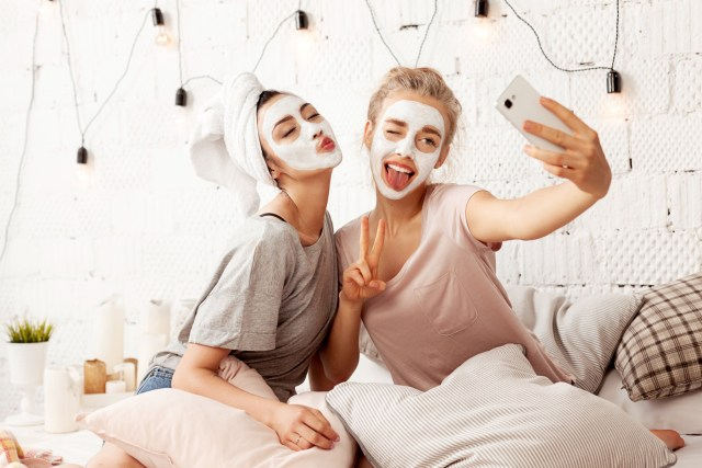 Two girls wearing face masks and taking a selfie