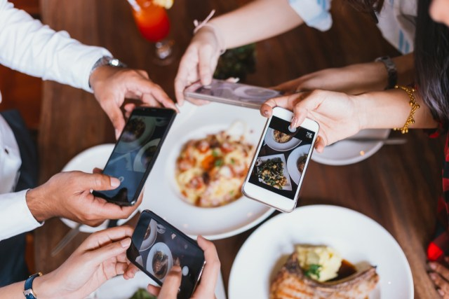A group of friends out eating taking pictures of their food