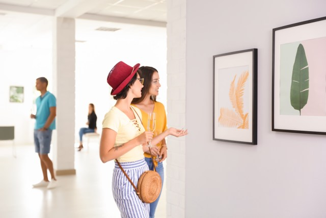 Two women looking at paintings in an art museum