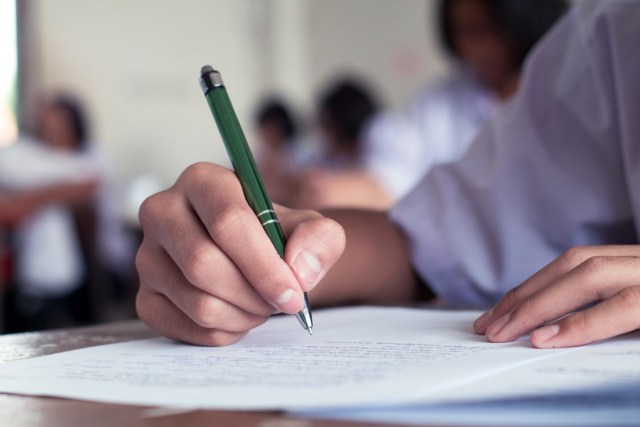 Close-up of person writing with a pen on a piece of paper