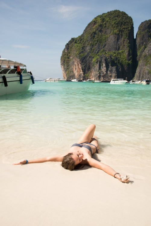 Young woman sun bathing in the sand