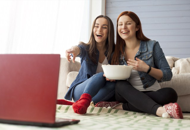 Two girls watching Netflix and eating popcorn