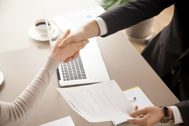 Two people making an agreement and shaking hands on it