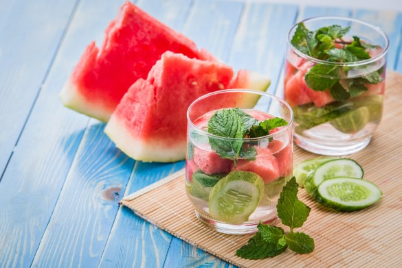 Glass of water with cucumber, watermelon and mint surrounded by watermelon slices