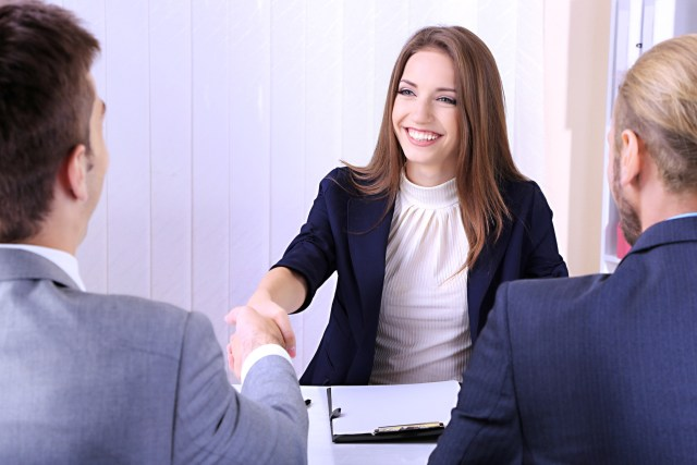 Young business woman smiling and shaking hands with interviewer