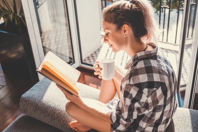 Girl reading by a window and holding a cup of coffee
