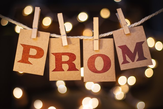 "A ""Prom"" sign hung up with fairy lights in the background"