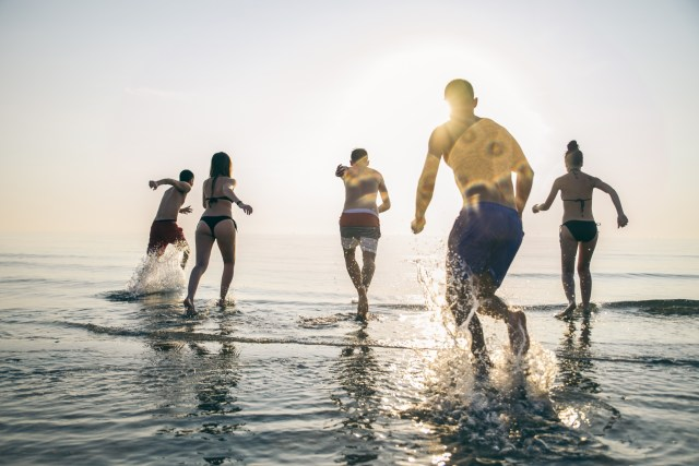 A group of friends running into the ocean